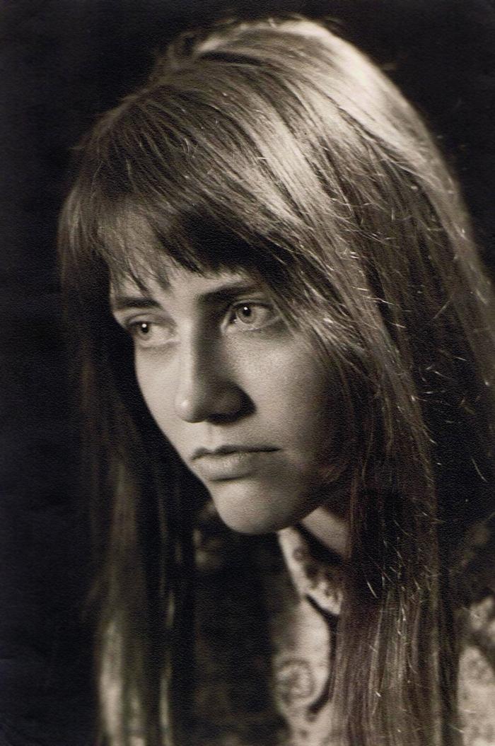 Junge Frau mit langen, dunklen Haaren schaut melancholisch an der Kamera vorbei.