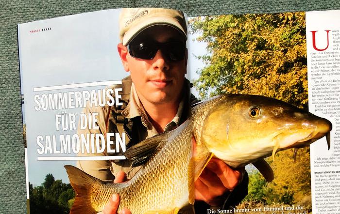 Angeler mit Kappe und Sonnenbrille, der einen großen Fisch in Händen hält