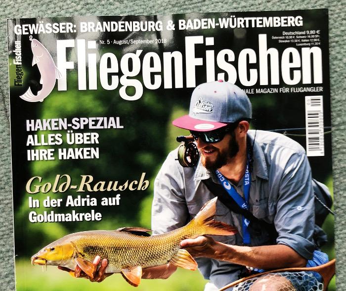 Angler mit Kappe und Sonnenbrille, der an einem Fluss einen Karpfen in der Hand hält