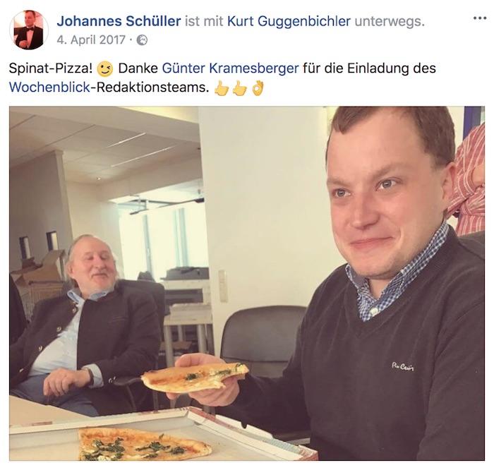 Zwei Männer sitzen an einem Tisch, einer isst Pizza