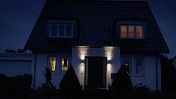 Standbild aus dem Imagefilm der Funke Mediengruppe: Ein Mann geht um ein Haus, es ist dunkel.