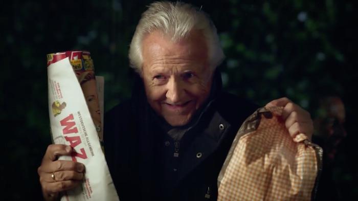 Standbild aus dem Imagefilm der Funke Mediengruppe: Opa schaut durchs Fenster und hält grinsend eine Tüte Brötchen und die WAZ hoch