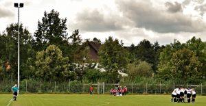 Totale eines Fußballplatzes, links steht der Schiedsrichter in der Spielfeldmitte, rechts die Mannschaft im Kreis.