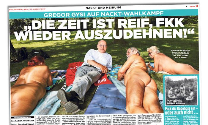 """Gregor Gysi liegt in Hose, Hemd und Schuhen auf einem """"Bild""""-Handtuch zwischen drei auf dem Bauch liegenden FKK-Freunden und grinst"""