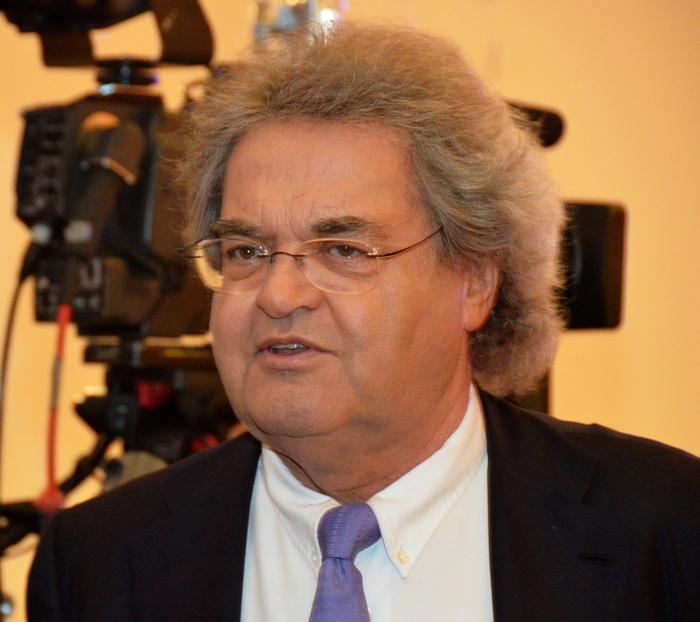 Gewichtiger Mann mit grauen langen Haaren, Brille, Anzug.