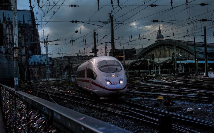 Ein ICE vor dem Kölner Hauptbahnhof, viele Gleise und Oberleitungen