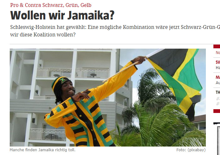 Jamaikaner mit Jamaika-Flagge, Jamaika-Pulli und Jamaika-Mütze