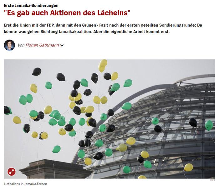 Schwarze, gelbe und grüne Luftballons, die über das Reichstagsgebäude fliegen