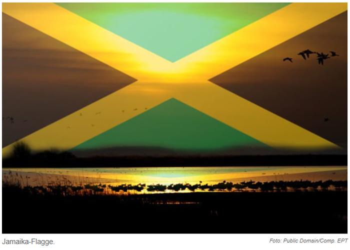 Sonnenuntergang am Strand; am Himmel ist (mit Photoshop eingefügt) eine Jamaika-Flagge zu sehen