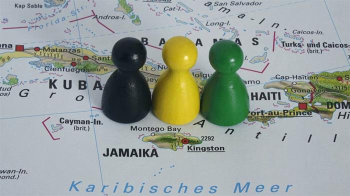 Schwarzes, gelbes und grünes Mensch-ärgere-dich-nicht-Männchen auf einer Landkarte, die Jamaika zeigt