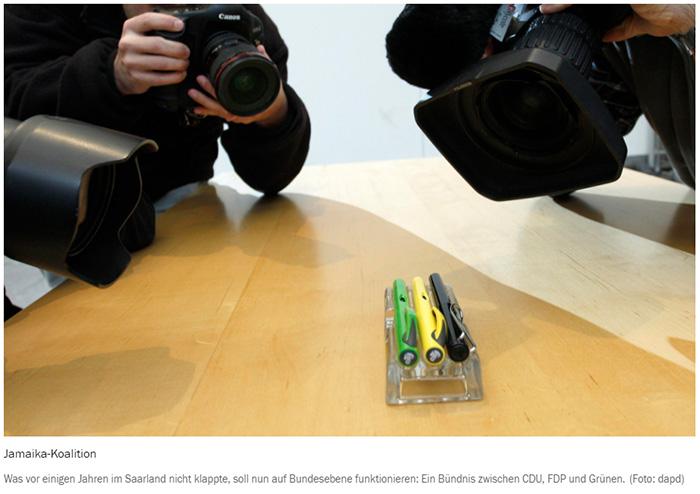Mehrere Fotografen und Kameramänner, die einen schwarzen, einen grünen und einen gelben Füller auf einem Tisch filmen und fotografieren