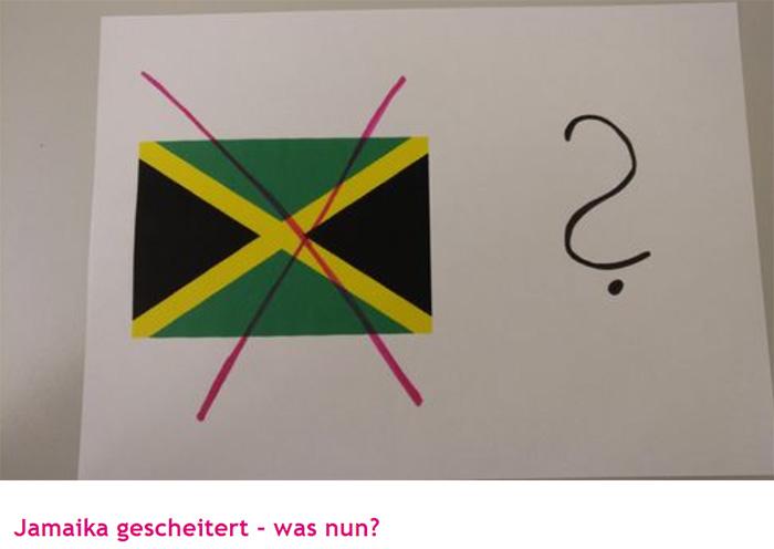 Auf einem Blatt Papier aufgemalt: Eine durchgestrichene Jamaika-Flagge, daneben ein Fragezeichen