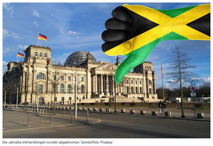 Eine mit Jamaika-Farben angemalte Hand, die vor dem Reichstagsgebäude den Daumen nach unten zeigt