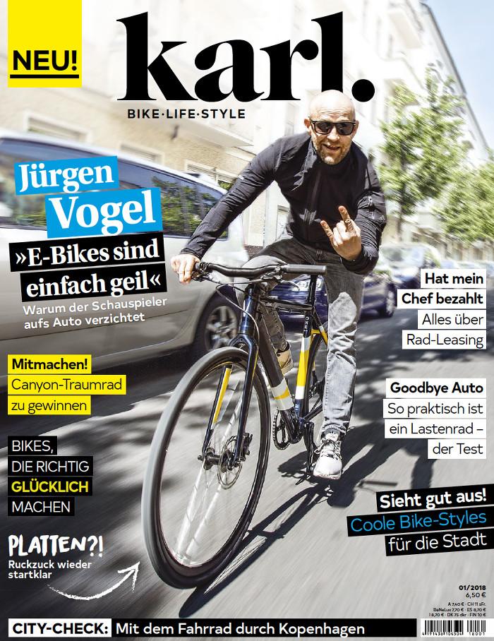 Jürgen Vogel (mit Glatze und Sonnenbrille) fährt Fahrrad und zeigt dabei Teufelshörner mit der Hand.