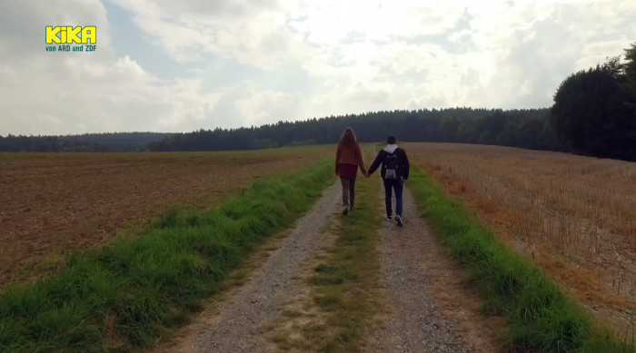 Ein junges Paar läuft Hand in Hand über einen Feldweg.