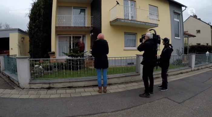 Kamermann, Tonassistent und Reporerin befragen eine Frau in ihrem Vorgarten