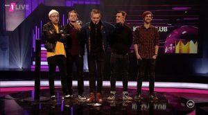 Fünf Männer stehen nebeneinander auf einer Bühne, einer redet in ein Mikrofon