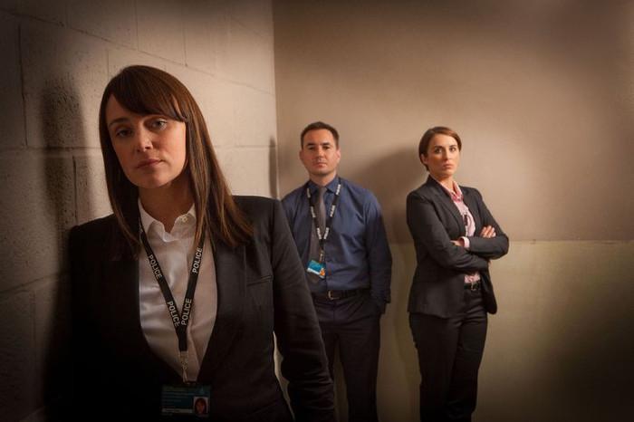 Eine Frau lehnt vorne links an der Wand, hinten stehen zwei weitere Personen, ein Mann und eine Frau, alle blicken ernst in die Kamera.