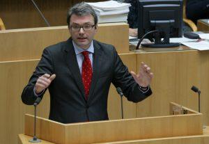 Mann mit Brille, Anzug und roter Krawatte hält eine Rede an einem Pult.