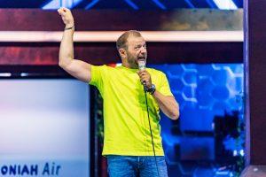 Mann in gelbem T-Shirt halt sich Mikrofon vors komische Gesicht.