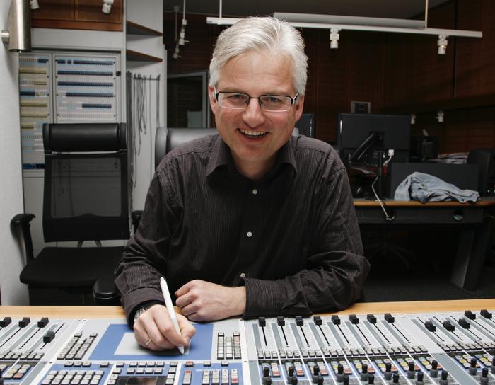 Mann mit grauem Haar und Brille sitzt an einem Tonmischpult, blickt in die Kamera und lacht.