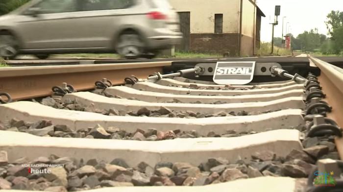 Gleis an einem Bahnübergang, im Hintergrund fährt gerade ein Auto drüber.
