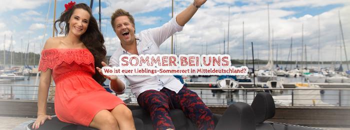 """Titelbanner der MDR-Serie """"Sommer bei uns"""", zu sehen sind zwei lachende Moderatoren, ein Mann und eine Frau, an einem Hafen."""