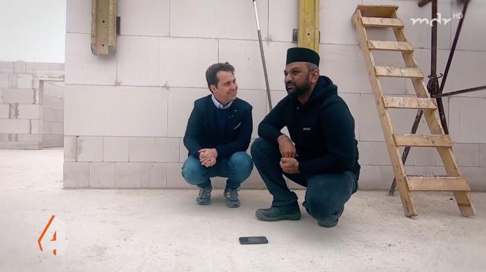 Zwei Männer hoclen in einem weißen Rohbau einer Moschee.