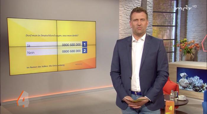 """Moderator steht neben Bildschirm mit der Frage: """"Darf man in Deutschland sagen, was man denkt?"""""""