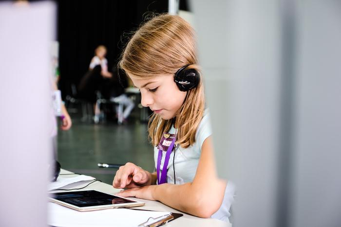 Mädchen mit Kopfhörern tippt auf einem Tablet