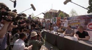 Dutzende Reporter scharen sich um einen langen Tisch, an dem Vertreter der NPD sitzen.