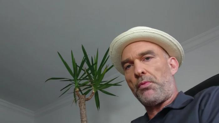 Mann mit Hut vor Yuccapalme