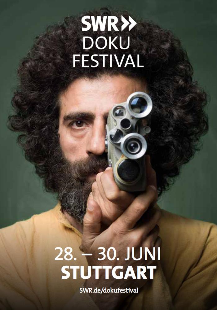 """Plakat des """"SWR Doku Festivals"""" in Stuttgart: Mann mit schwarzen Locken und schwarzem Bart schaut durch eine alte Kamera"""