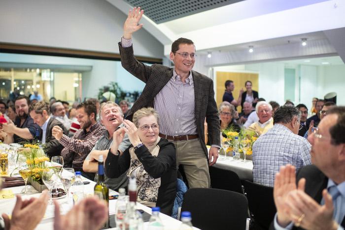 Mann mit Brille und im Anzug geht winkend durch Tischreihen in einem Saal.
