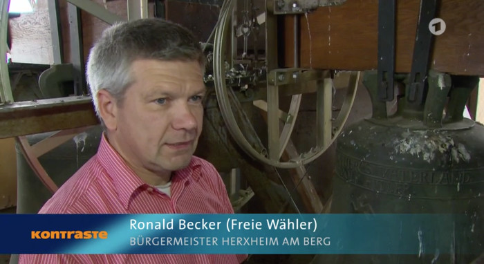 Mann mit grauen Haaren und rötlichem Hemd steht im Glockenturm der örtlichen Kirche