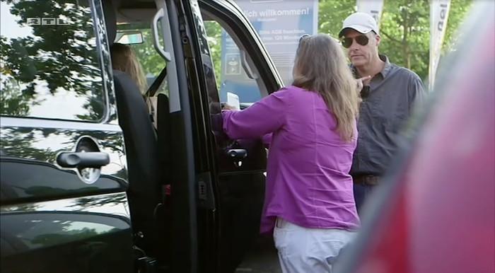 Frau mit lilafarbenem Hemd und Mann mit weißer Kappe und Sonnenbrille stehen an einem dunklen Van.