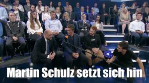 Martin Schulz sitzt am Fuß einer Tribüne in einem Fernsehstudio und redet mit Zuschauern.