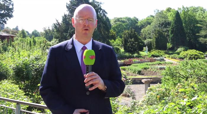 """Ein Mann steht im Anzug in einem weitläufigen Garten und spricht in ein Mikrofon des Senders """"MDR Jump""""."""