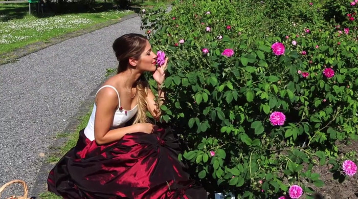 Eine Frau hockt in einem üppigen Kleid vor einem Rosenstrauch und reicht daran.