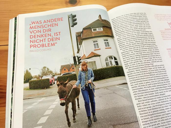 """Frau geht mit einem Esel über einen Fußgängerüberweg, daneben der Text: """"Was andere Leute über dich denken, ist nicht dein Problem"""""""