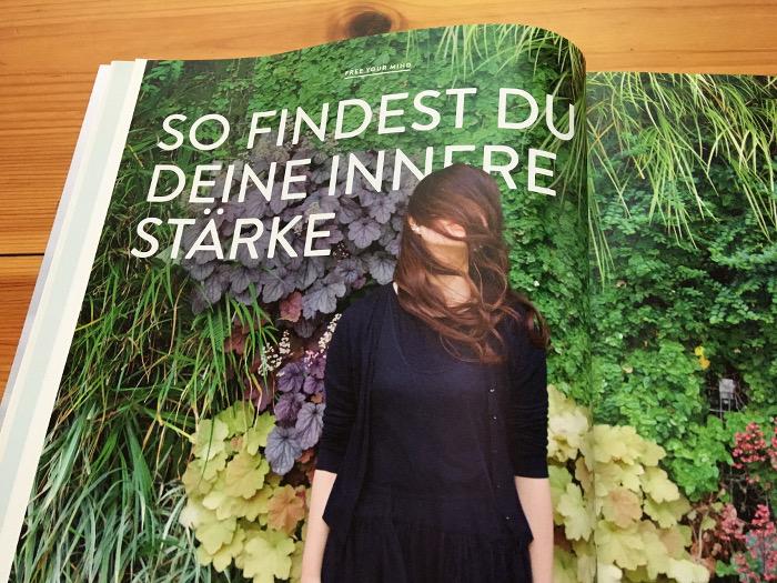 """Frau steht vor einer grün beflanzten Wand, hat Haare vor dem Gesicht, daneben der Text: """"So findest du deine innere Stärke"""""""