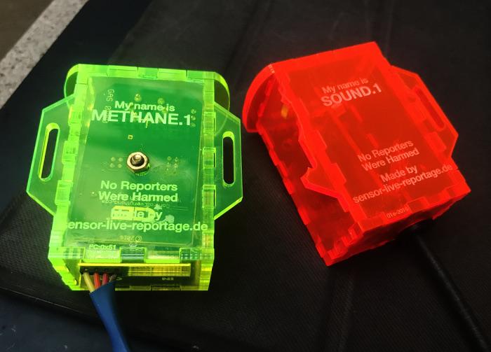 Zwei kleine Plastik-Dosen mit Computerchips und Kabeln, eins in neongrün, eins in rot