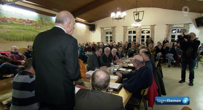 Gemeindesaal voll mit Menschen an Tischen, vor Kopf steht ein älterer Mann und redet