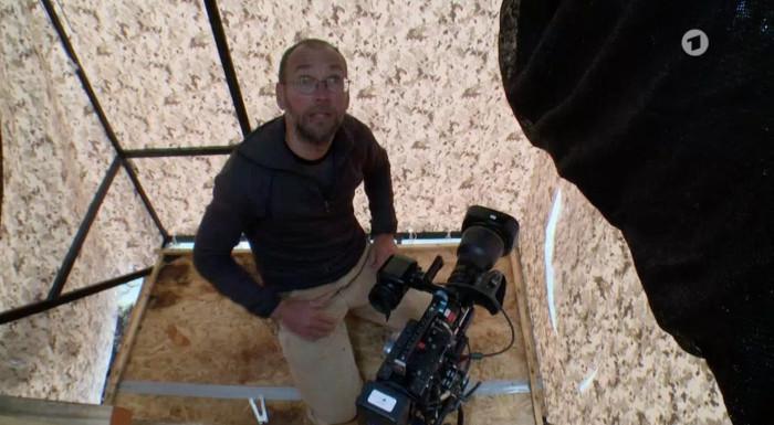 Mann hockt mit seiner Kamera in einem kleinen Verschlag, in den ein Lock geschnitten wurde – zum Rausfilmen.