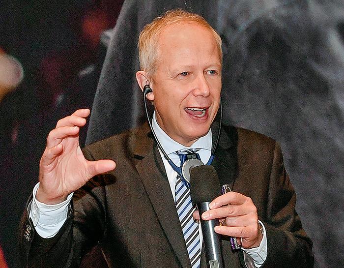 Blonder Mann im Anzug, der in ein Mikrofon spricht.
