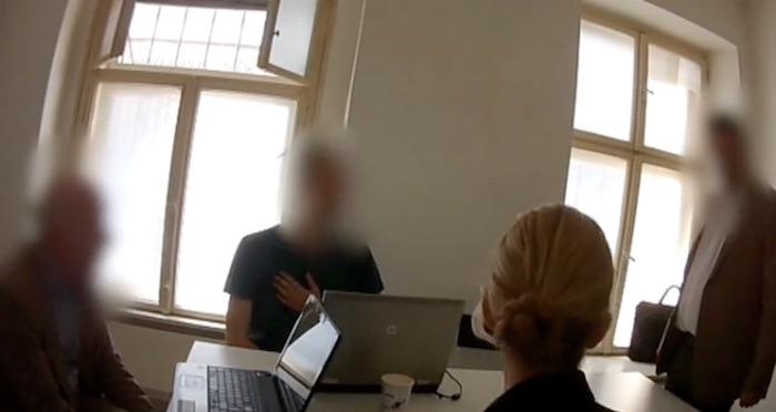 Vier Menschen sitzen an einem Konferenztisch, drei Gesichter sind verpixelt, die Reporterin sieht man nur von hinten.