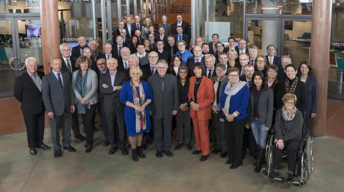 60 Leute haben sich zu einem Gruppenfoto aufgestellt