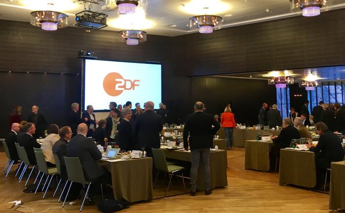 Großer Saal mit Tischen, an denen Menschen sitzen oder stehen. Im Hintergrund eine Leinwand mit ZDF-Logo.